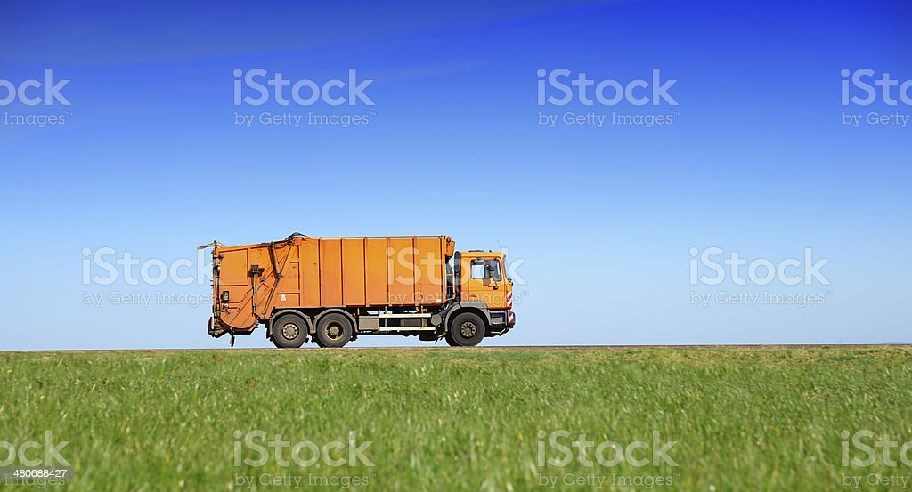Garbage truck drives on country road through fields royalty-free stock photo