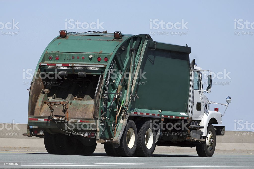 A garbage truck driving along an open road stock photo