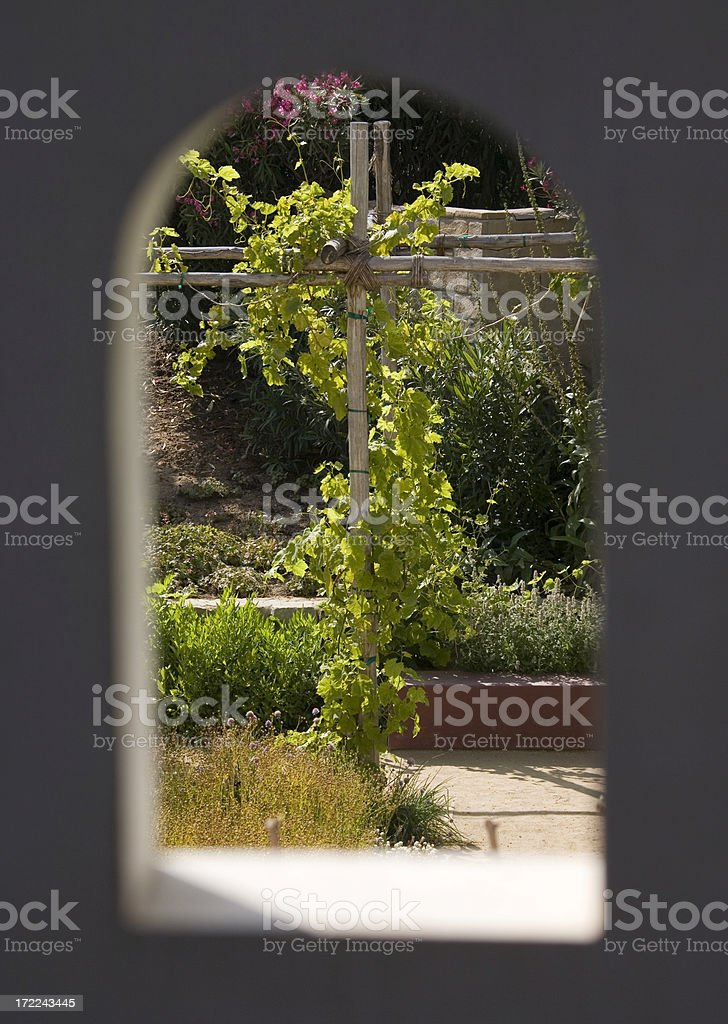 Garden area seen through arch opening in wall royalty-free stock photo