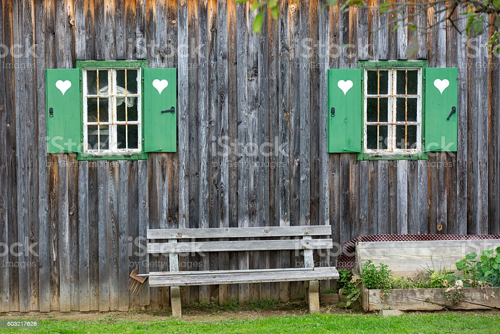 garden bench in front of a cottage in styria stock photo
