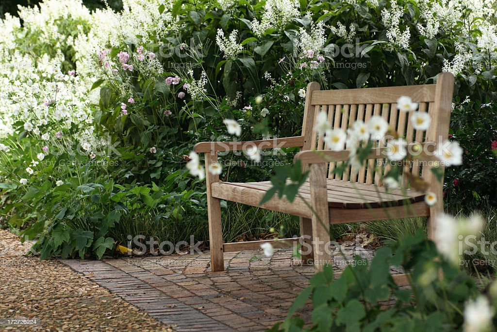 Garden bench in shaded garden with flowers royalty-free stock photo