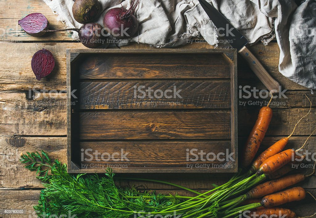 Garden carrots and beetroots with wooden tray in center stock photo