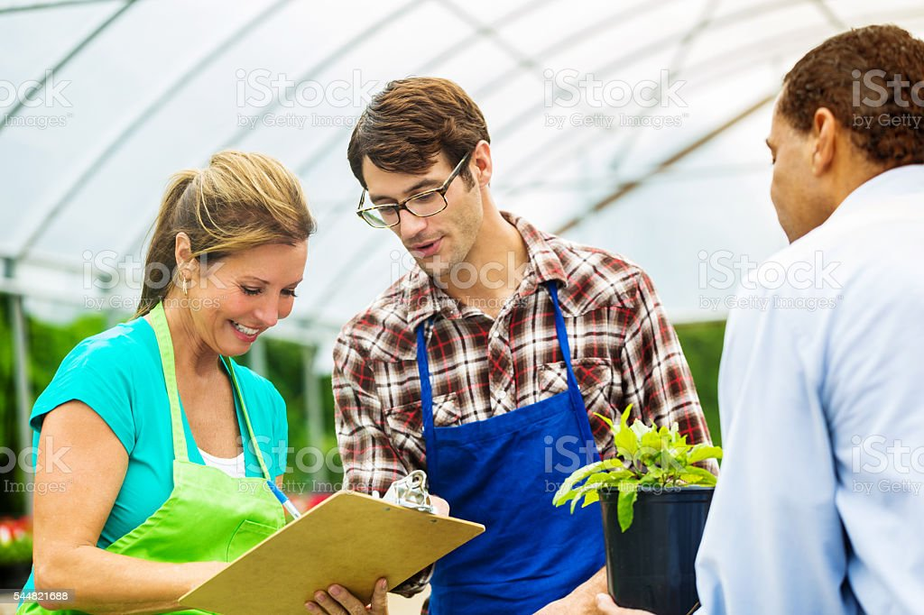 Garden center employees writing up a purchse for a customer stock photo