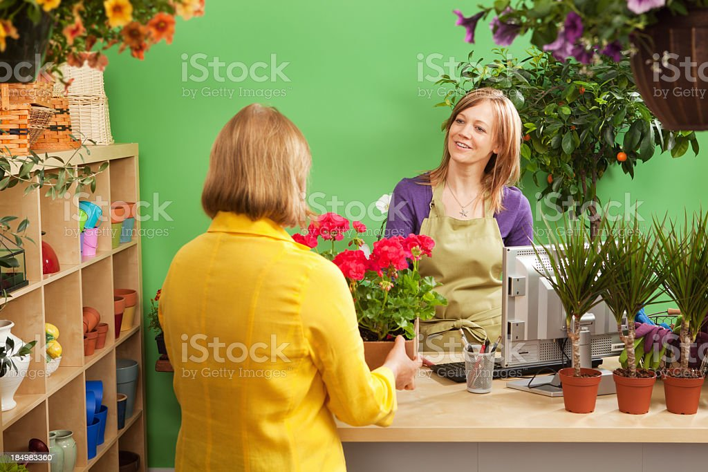 Garden Center Shop Owner Serving Customer in Retail Store Hz royalty-free stock photo