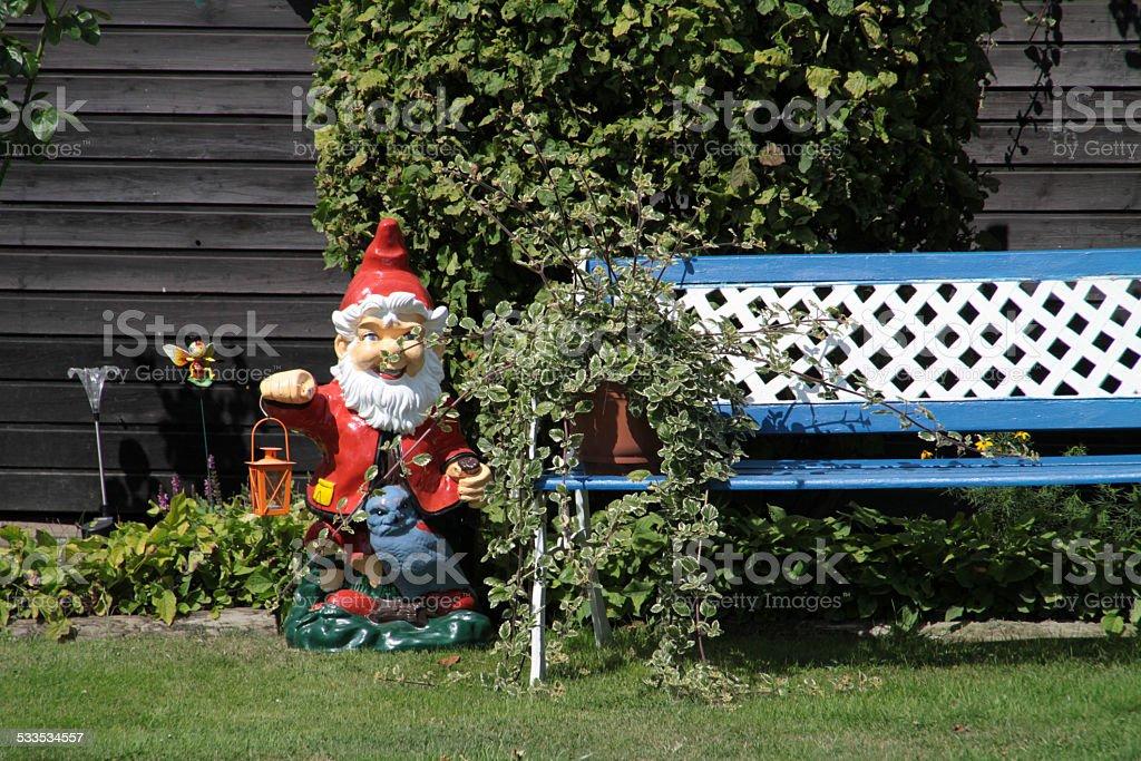 Garden gnome and garden bench stock photo