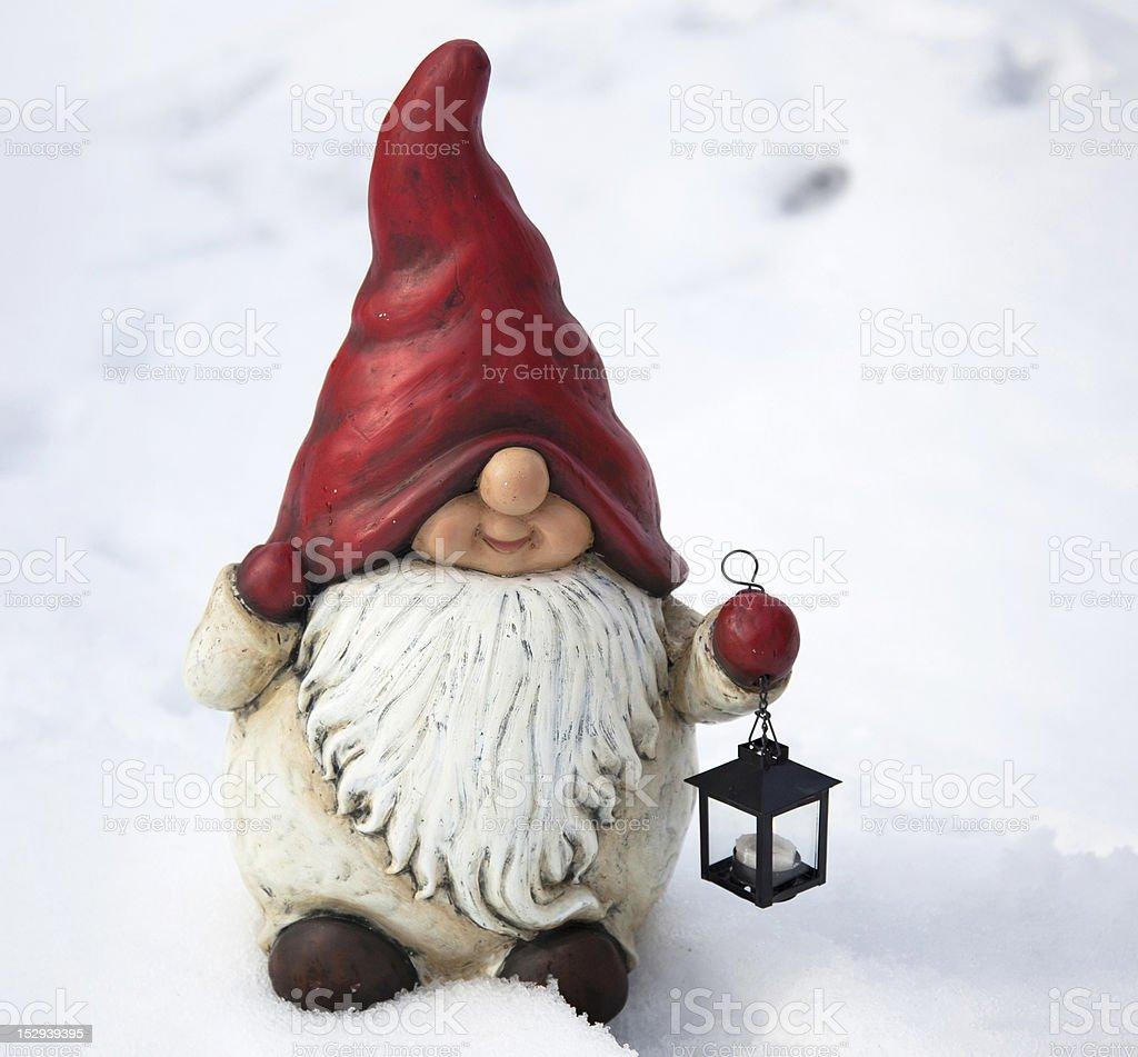 Garden gnome in the snow stock photo