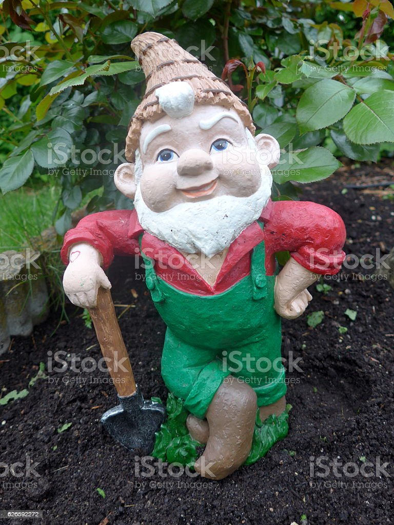 Garden gnome with shovel at work stock photo