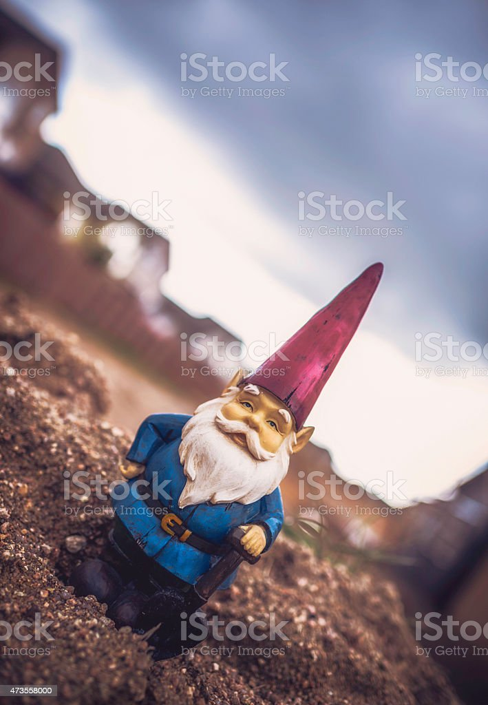 Garden gnome with shovel stands on soil at construction site stock photo