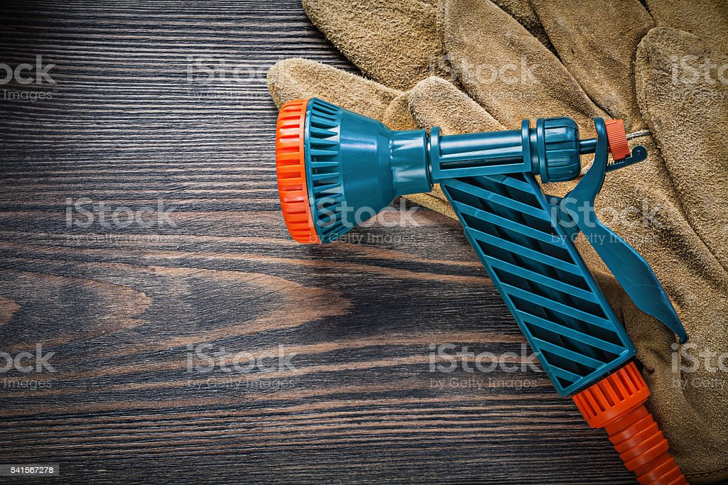 Garden hose nozzle protective gloves on vintage wood board agric stock photo