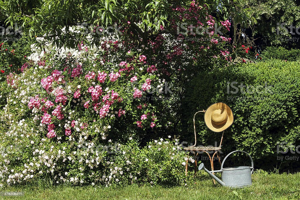 Garden idyll with iron chair and sun hat stock photo