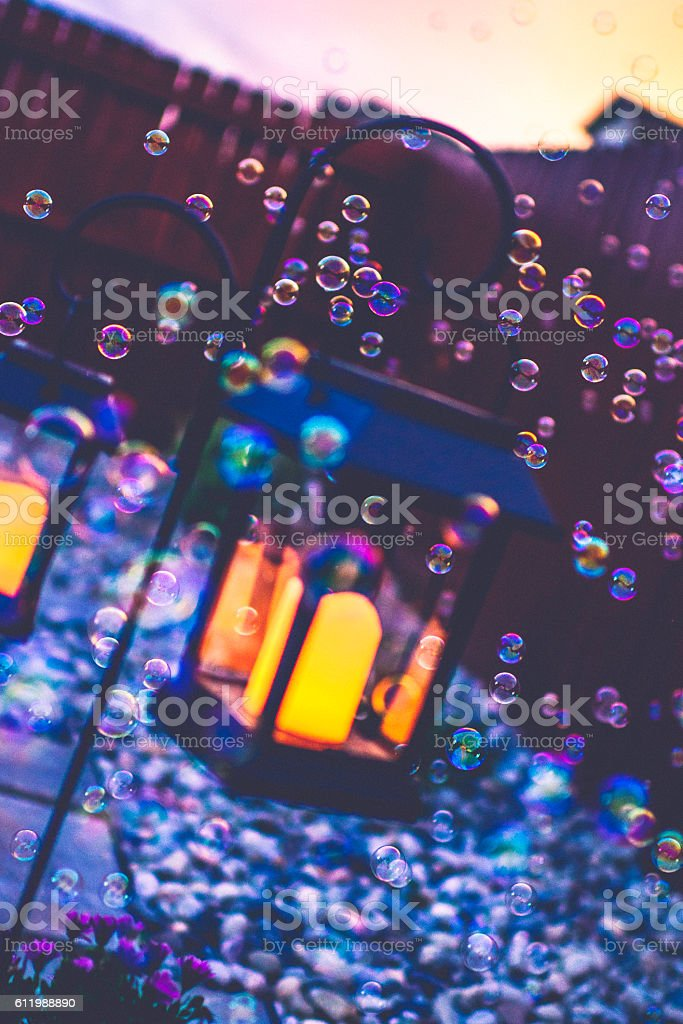Garden lanterns with glowing candles and bubbles at dusk stock photo