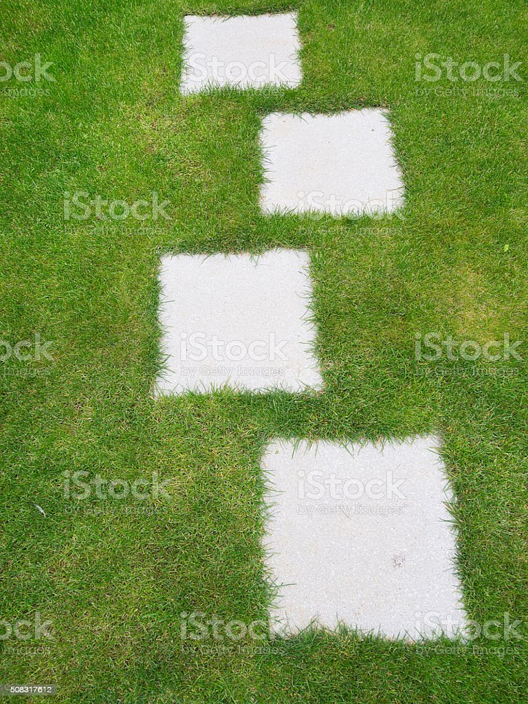 Garden lawn grass background with path of grey tiles inset. stock photo