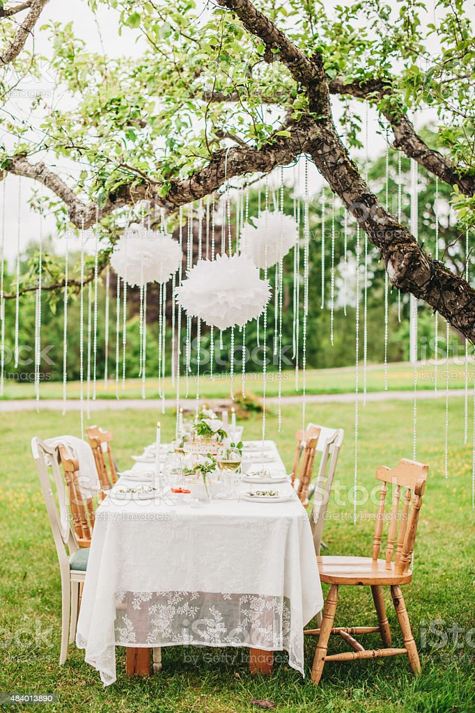 Garden party arrangement with decorations hanging from tree. stock photo