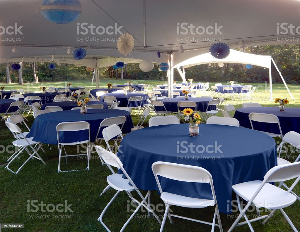 Garden party setup with tables, chairs, tents.  Blue.  White. stock photo