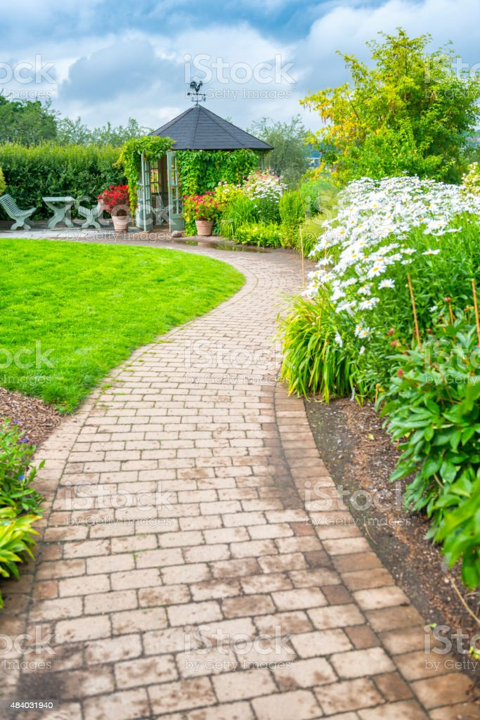 Garden path leads to gazebo stock photo