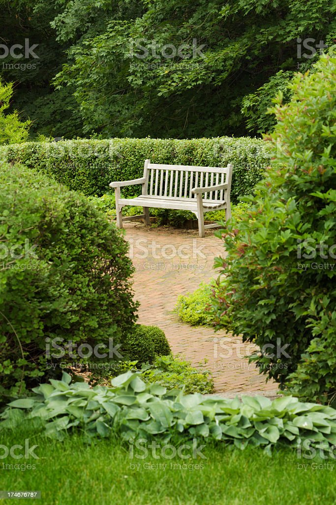 Garden Patio Landscaped with Teak Wooden Bench, Brick Path, Bushes royalty-free stock photo