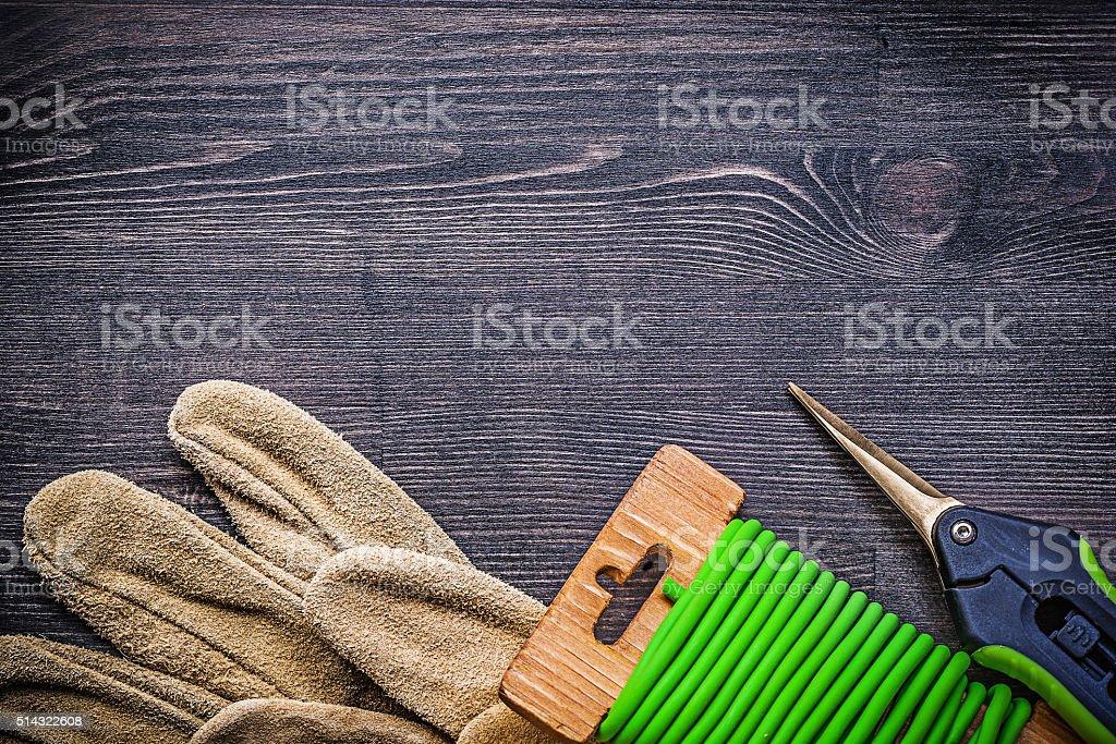 Garden pruner soft twist tie working gloves on vintage wood stock photo