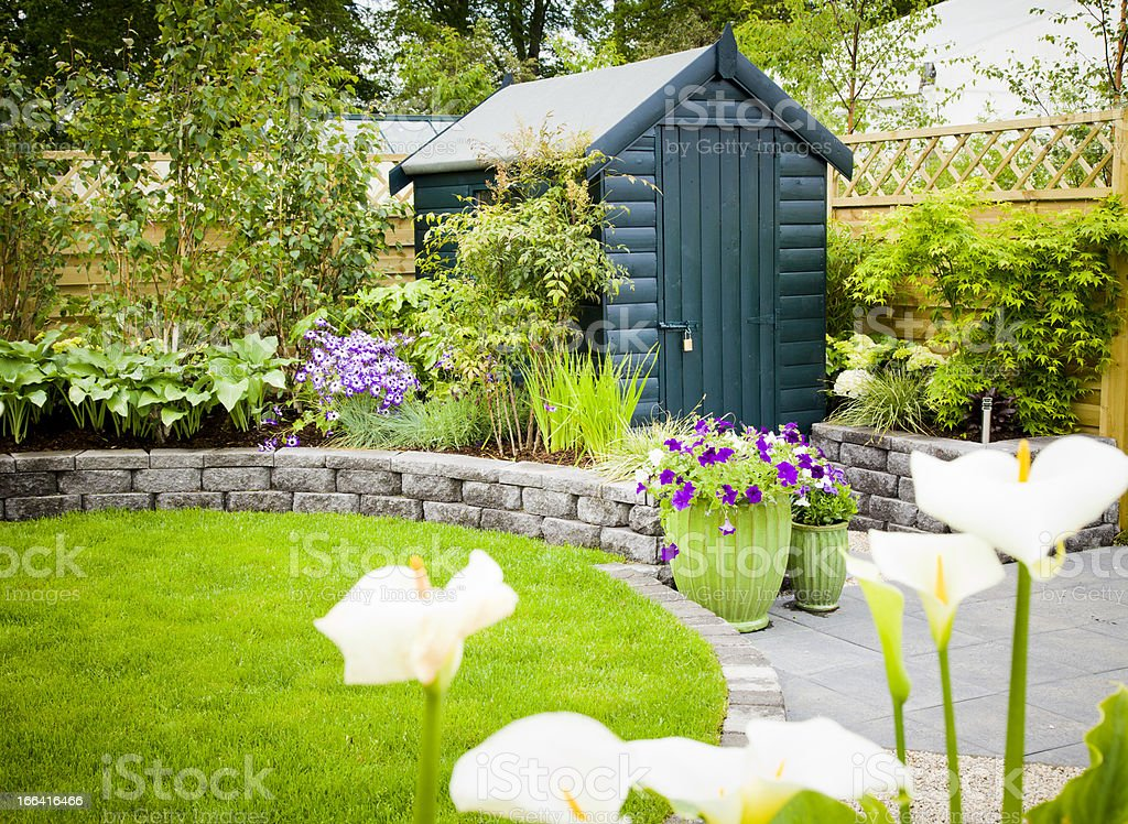 Garden shed in a beautiful green garden stock photo