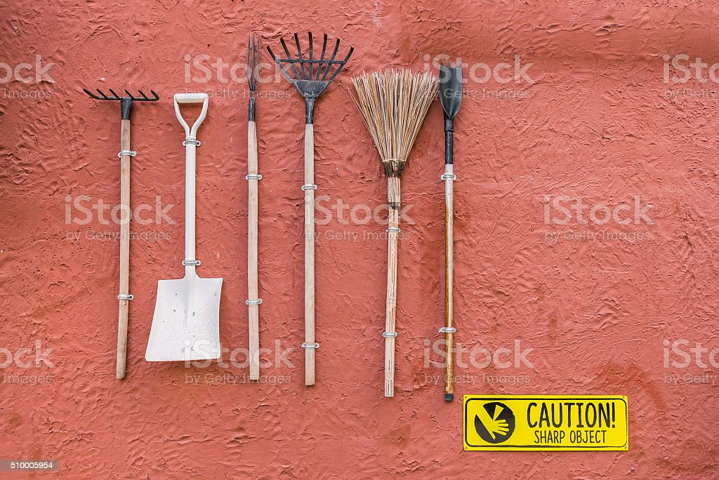 Garden tools hanging on the res wall with vintage feel stock photo