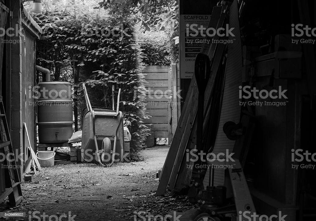 Garden wheelbarrow And Rainwater Tank Near Barn stock photo