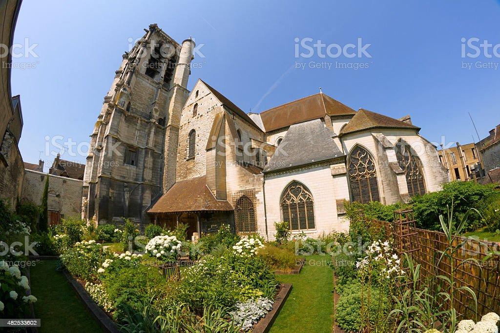 Garden with a medieval church stock photo
