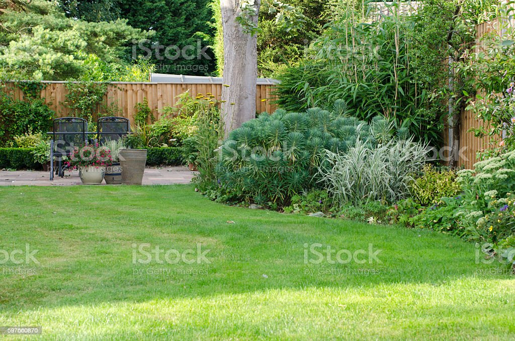 Garden with patio area, lawn and flowerbeds. stock photo