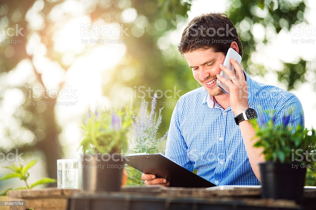 Gardener holding clipboard, making phone call, green sunny natur stock photo