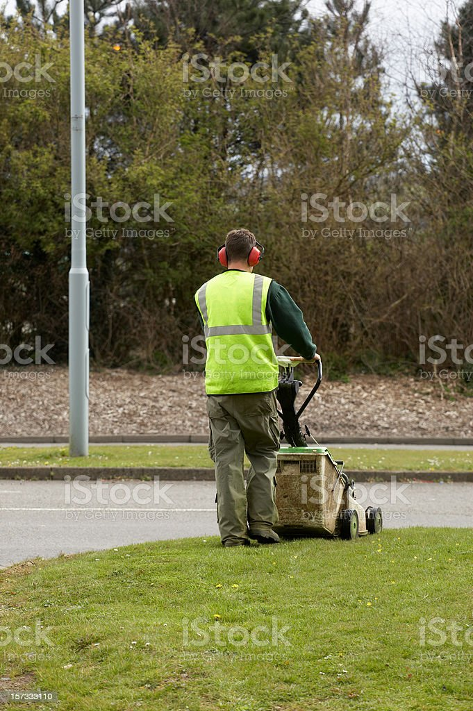 Gardener mowing grass verge d stock photo