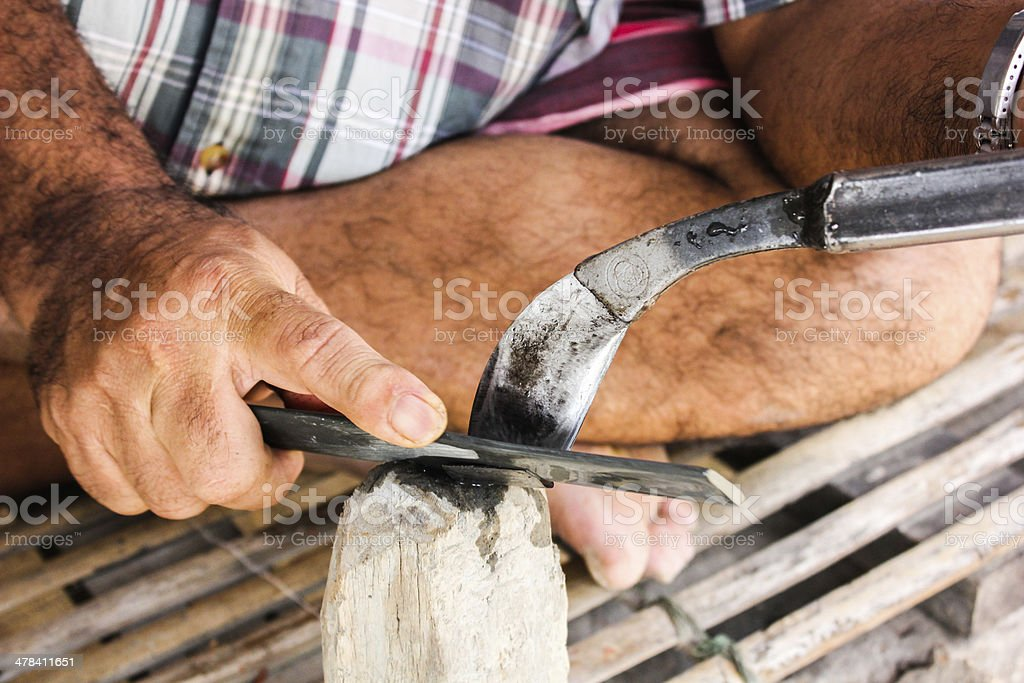 gardener rubber sharpening the knife with whetstone stock photo