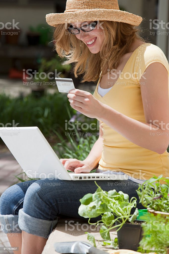 Gardener sitting outside using credit card and laptop royalty-free stock photo
