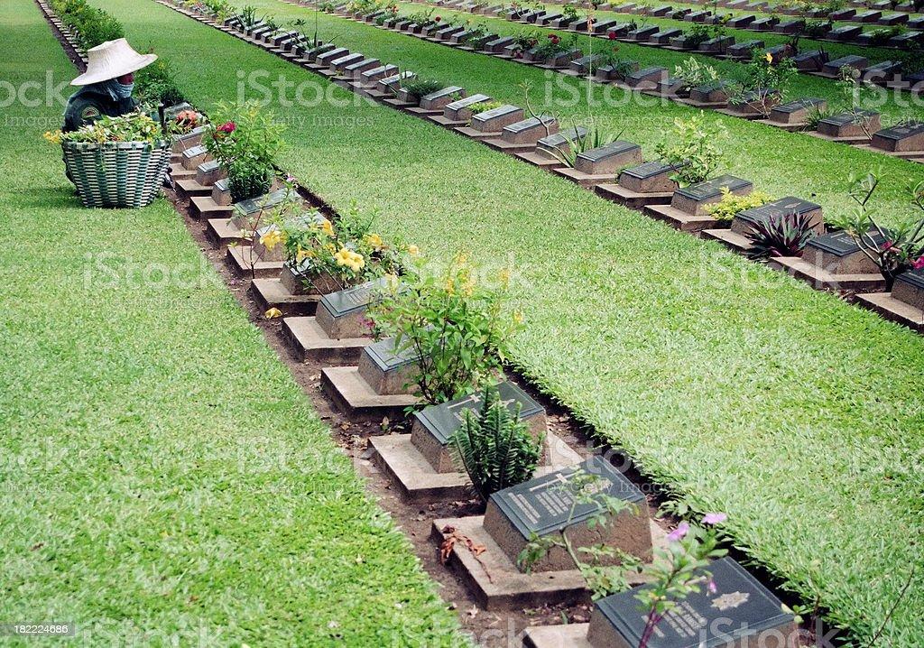 Gardener tending graves in Kanchanaburi Cemetery stock photo