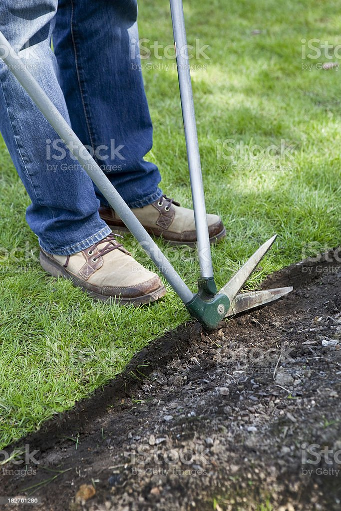 Gardener Trimming Lawn Edges with Shears royalty-free stock photo