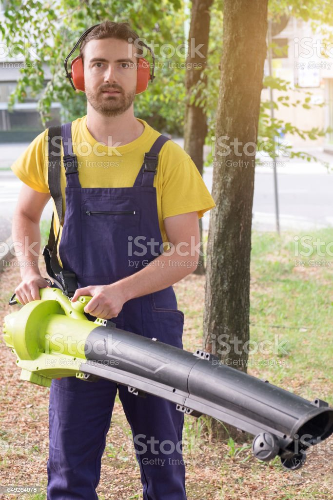 Gardener using his leaves blower in the garden stock photo