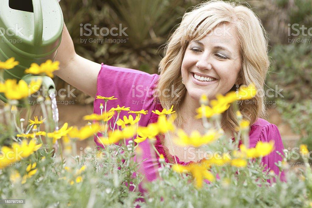 Gardener watering the plants smiling stock photo