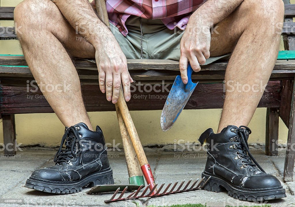 gardener with hairy legs resting on a bench stock photo