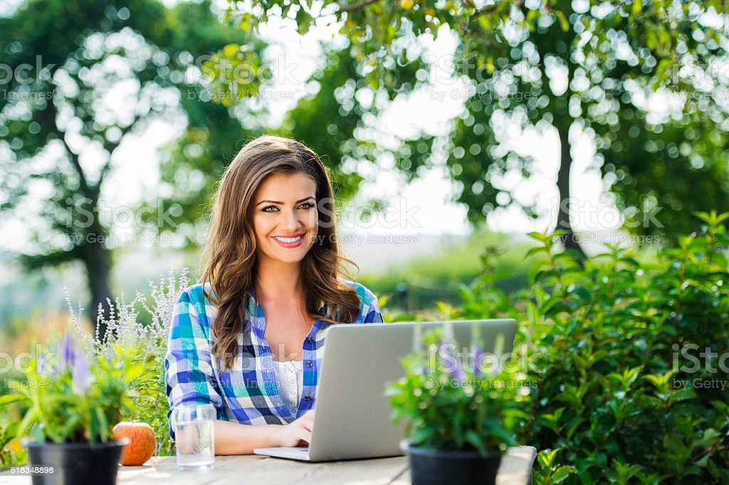 Gardener with notebook, sitting at the table, green nature stock photo