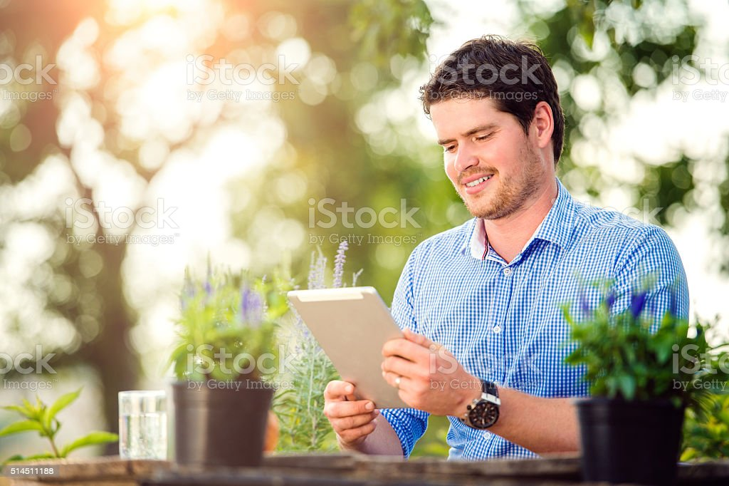 Gardener with tablet, sitting at the table, green nature stock photo