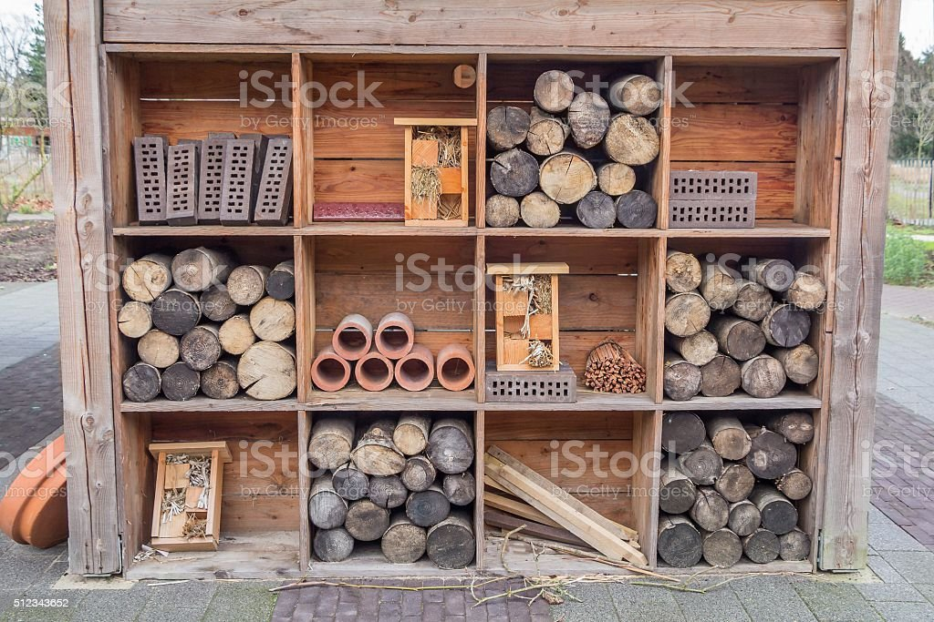 Gardenhouse constrruction with beehotels and tree truncks stock photo