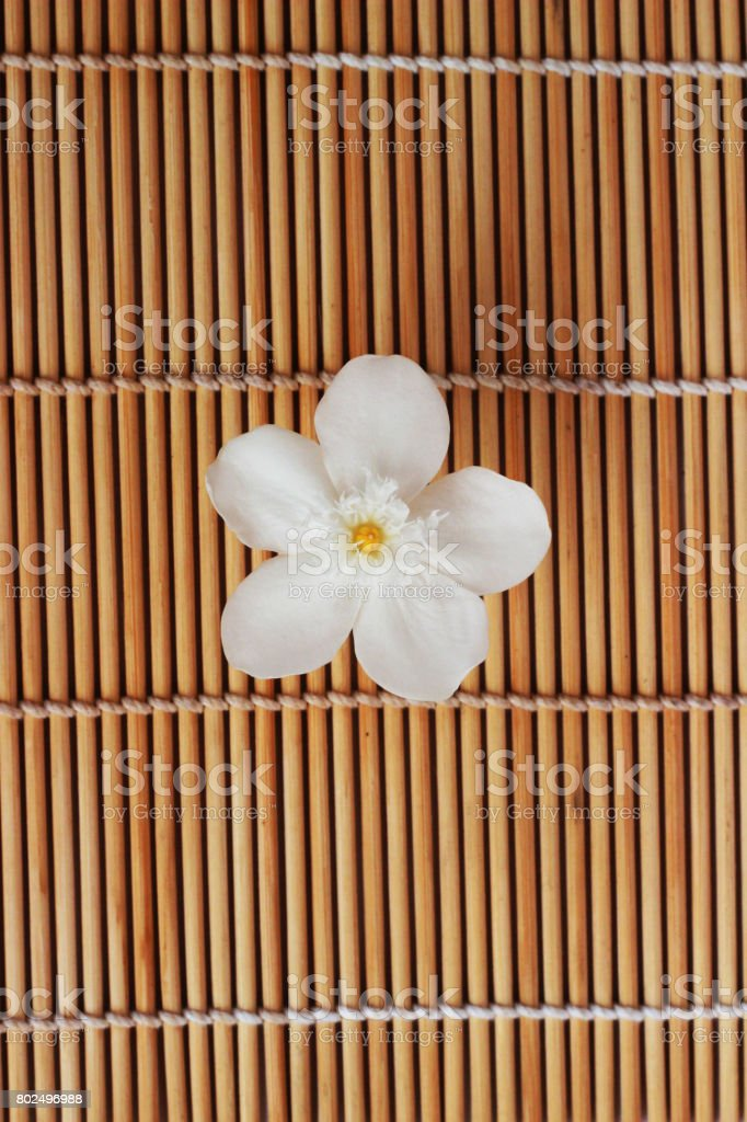 Gardenia white flowers placed on brown weave bamboo as background
