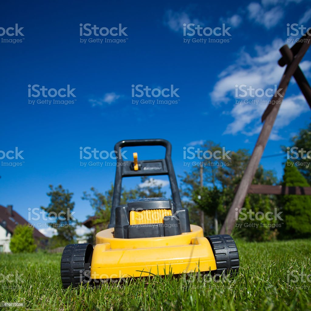 Gardening. Mowing lawn with yellow lawnmower stock photo