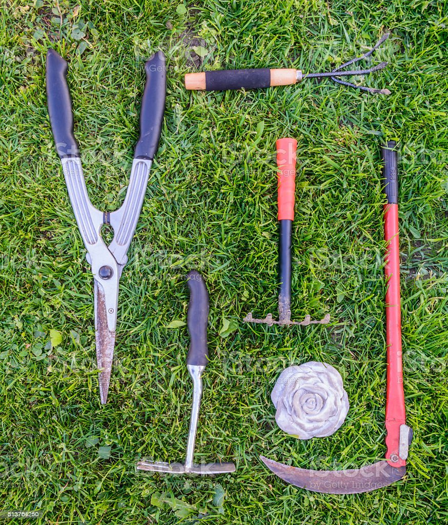 Gardening tools on green grass in the garden. stock photo