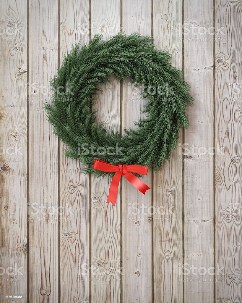 garland wreath with red ribbon on vintage wooden planks wall stock photo