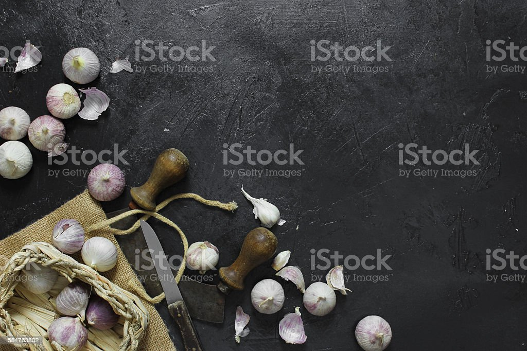 garlic and cutlery on dark background stock photo