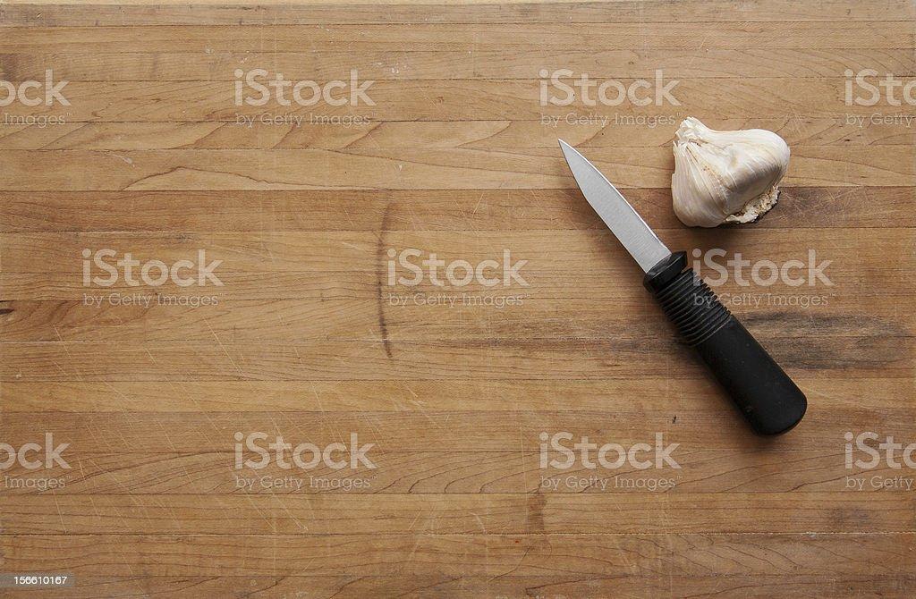 Garlic and Knife on a Worn Cutting Board stock photo