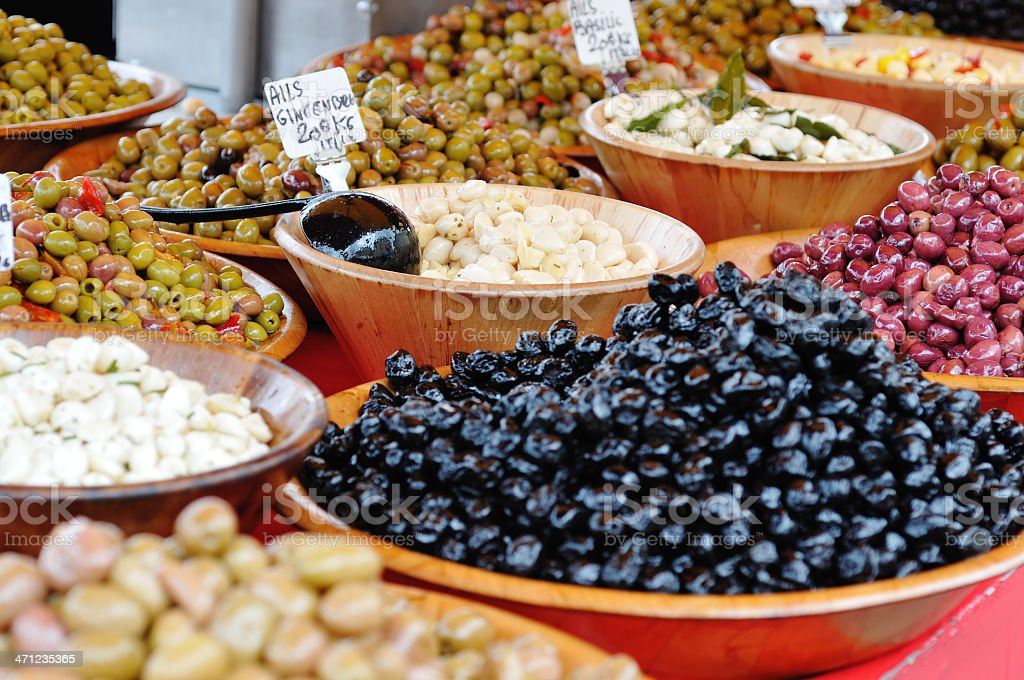 garlic cloves and olives on French market stall stock photo