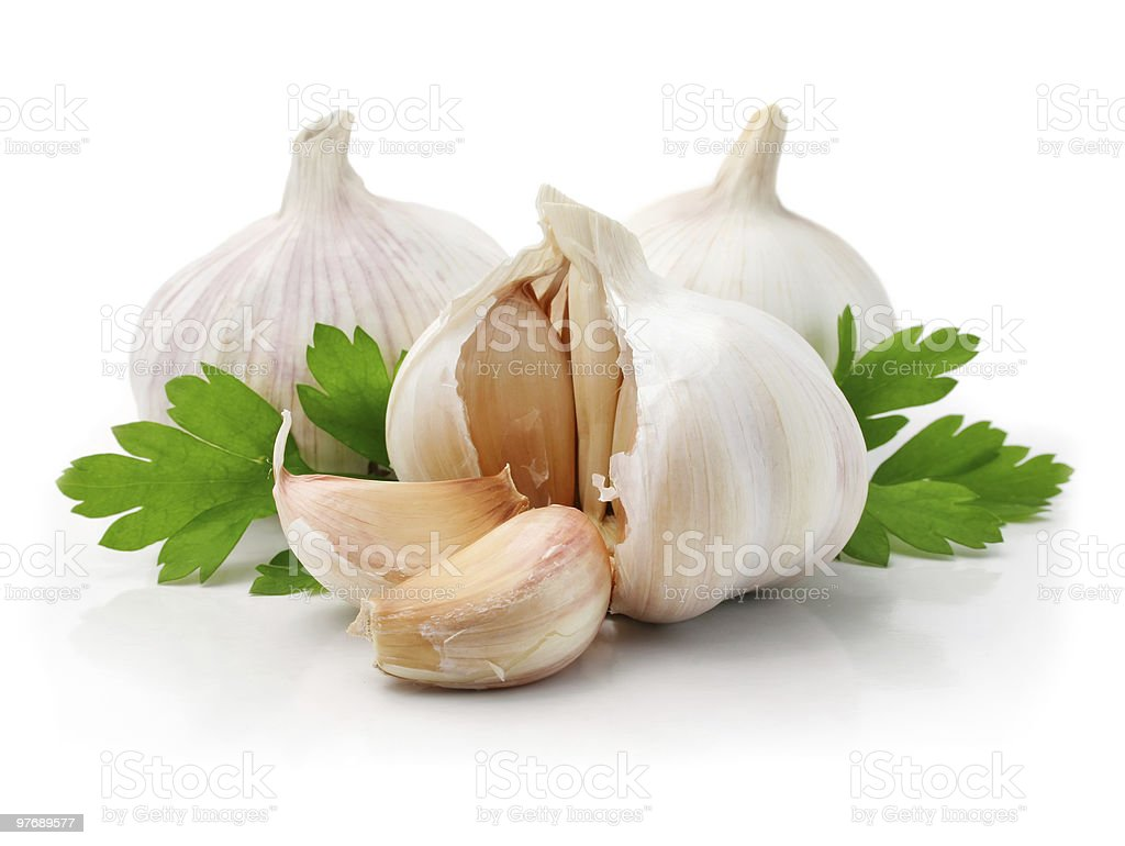 garlic fruits with green parsley leaves stock photo