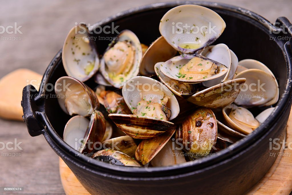 Garlic white wine clam in black pot on wooden tray stock photo