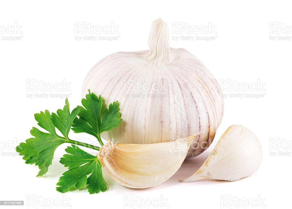 garlic with parsley leaves on a white background stock photo
