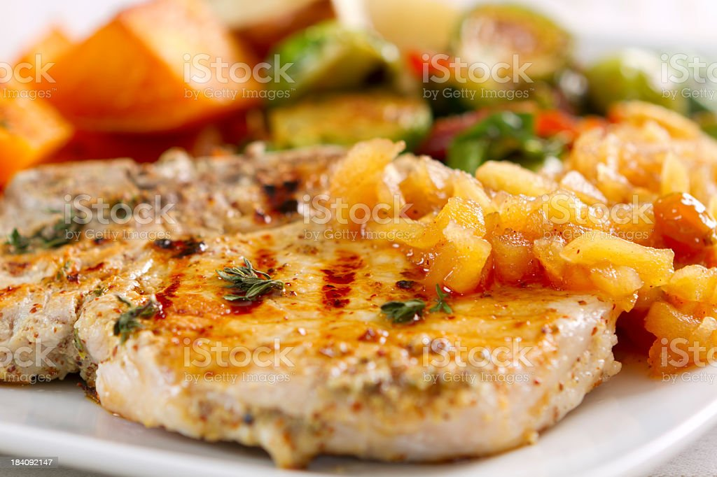 Garlic-herbed pork chops served with applesauce stock photo
