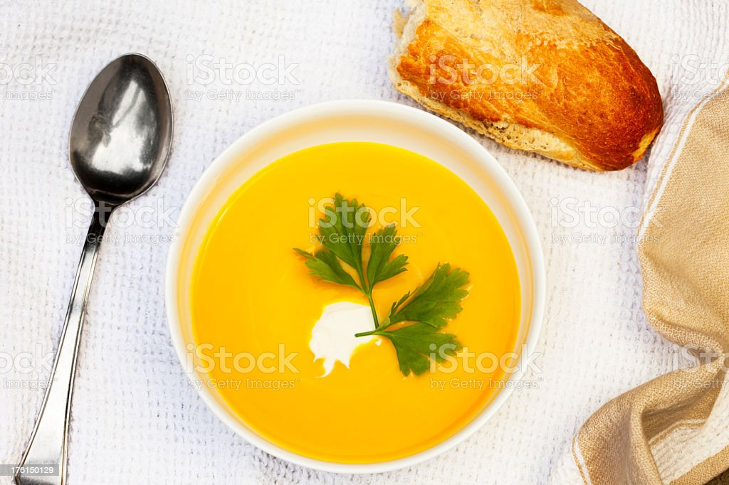 Garnished bowl of warm pumpkin soup on tablecloth royalty-free stock photo